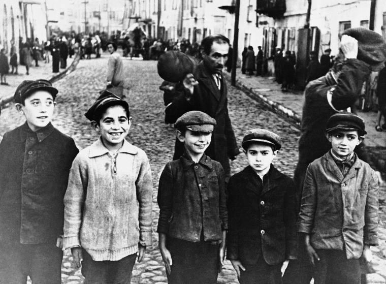 Men of the Lublin ghetto, behind boys, wear arm bands earmarking them as Jews, shown during the German occupation of Poland.