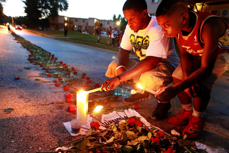 Image: Theo Murphy, left, of Florissant, Mo., and his brother Jordan Marshall, 11, light candles at a memorial on Canfield Drive in Ferguson, Mo.