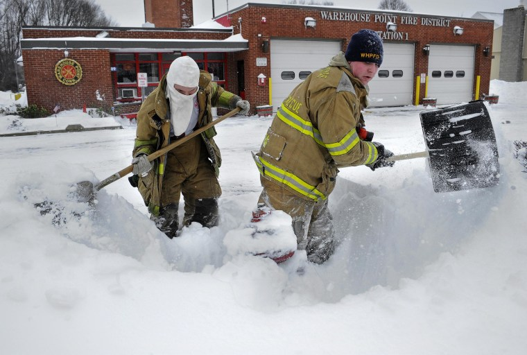 Image: Junior firefighter Adam Krach, left, and firefighter Steve Ellis of the Warehouse Point Fire Department dig snow from a hydrant outside their station in East Windsor, Conn.