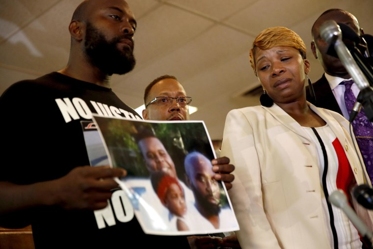 Lesley McSpadden, right, the mother of 18-year-old Michael Brown, watches as Brown's father, Michael Brown Sr., holds up a family picture of himself, his son, top left in photo, and a young child during a news conference Monday, Aug. 11, 2014, in Ferguson, Mo. Michael Brown, 18, was shot and killed in a confrontation with police in the St. Louis suburb of Ferguson, Mo,