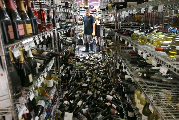 A worker looks at a pile of wine bottles that were thrown from the shelves at Van's Liquors following a reported 6.0 earthquake on Aug. 24, 2014 in Napa, California.