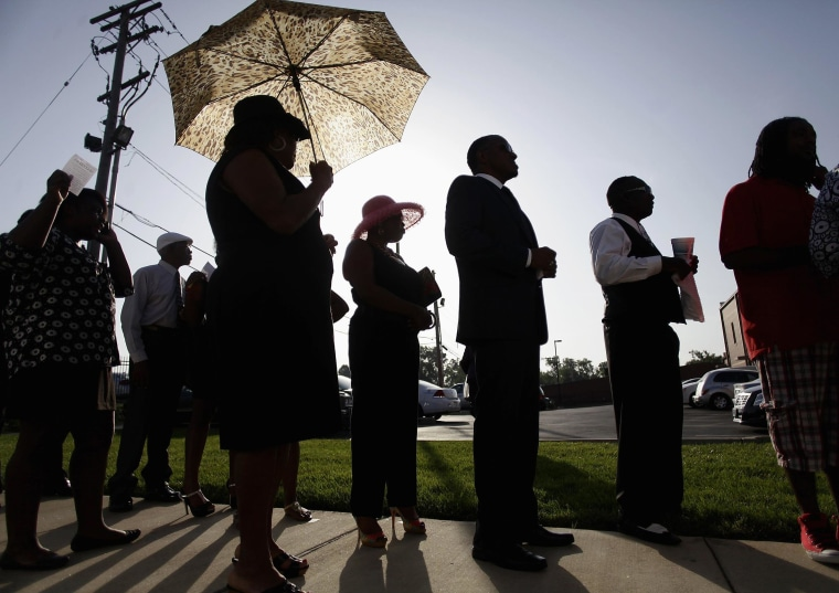 Image: People are silhouetted against the sun as they wait in line to attend the funeral for Michael Brown at Friendly Temple Missionary Baptist Church in St. Louis, Missouri