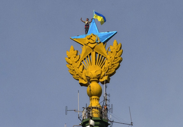Image: A worker takes a selfie before removing a yellow and blue Ukrainian flag attached by protesters on the top of a Stalin-era skyscraper in Moscow on Aug. 20.