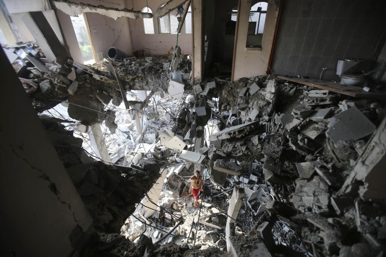 Image: Palestinian man inspects his house, which witnesses said was hit by an Israeli air strike, in Rafah in the southern Gaza Strip
