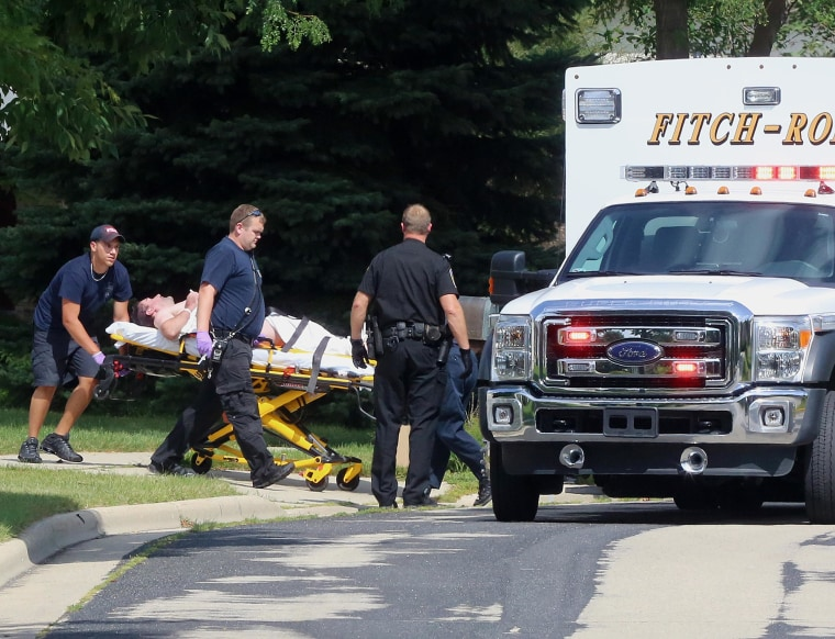 Image: Emergency personnel transport Andy Steele from his home in Fitchburg, Wis., where authorities said Steele's wife, Ashlee Steele and sister-in-law, Kacee Tollesfsbol, were found shot dead on Aug. 22