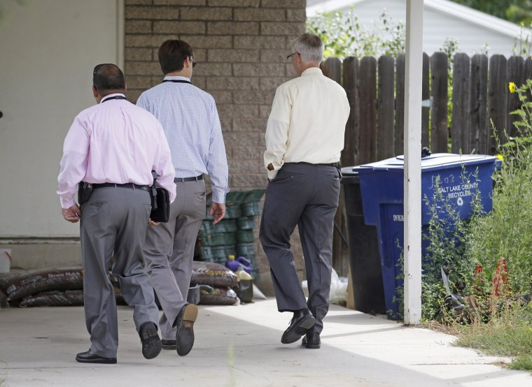Image: Police walk near garbage cans where a baby was found
