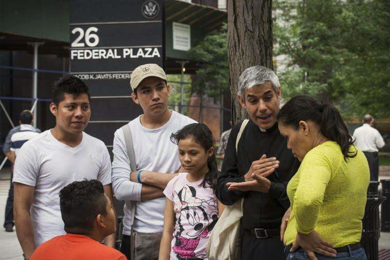 Image: File photo of Father Arias, an advocate with New Sanctuary Coalition of New York City, speaking with immigrants following their immigration hearings at the U.S. Federal Building in New York
