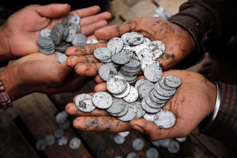 Indians sort coins offered by devotees to the river
