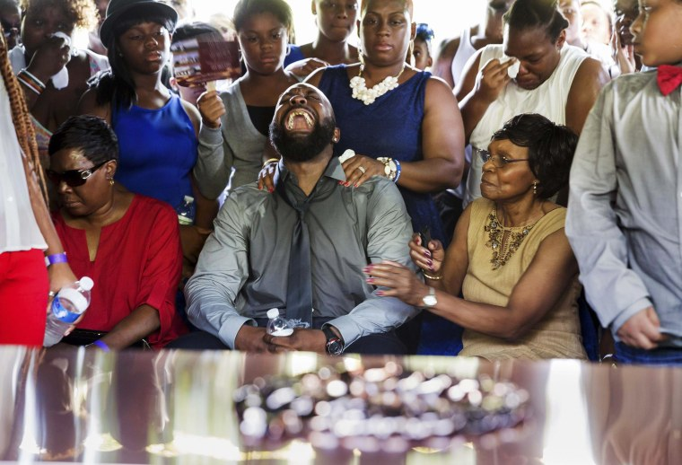 Image: Michael Brown Sr. yells out as his son's casket is lowered into the ground at St. Peter's Cemetery in St. Louis