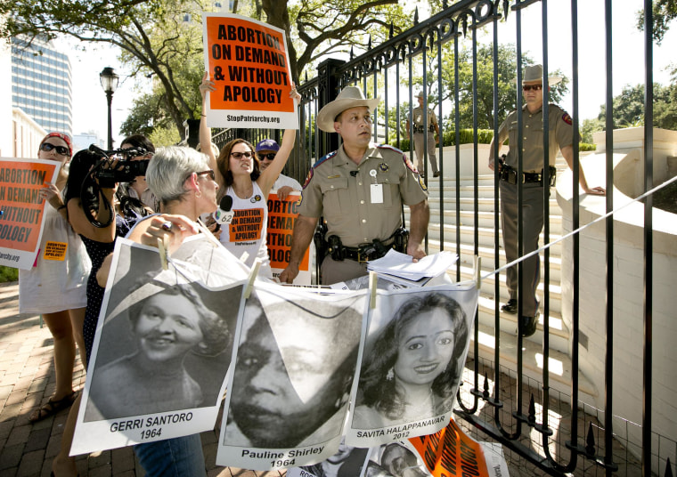 Image: Pro-abortion rights activists chant slogans while a Texas Department of Public Safety trooper removes their signs