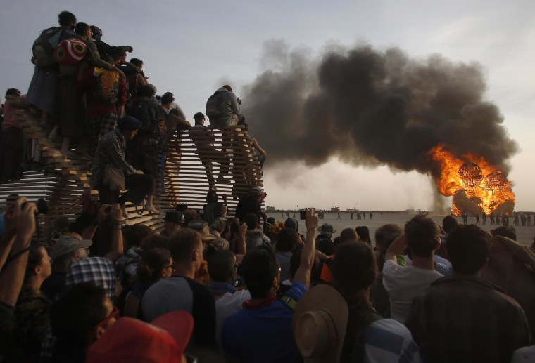 "Participants watch the art installation ""Embrace"" burn during the Burning Man 2014 ""Caravansary"" arts and music festival in the Black Rock Desert of Nevada, on Aug. 29."