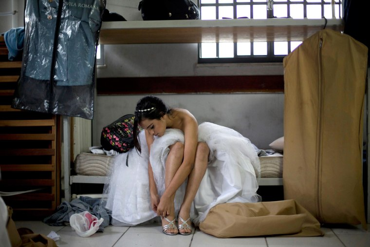 """Image: A teenage girl from the Santa Marta """"favela"""" slum puts on a pair of high heels for a debutante ball"""