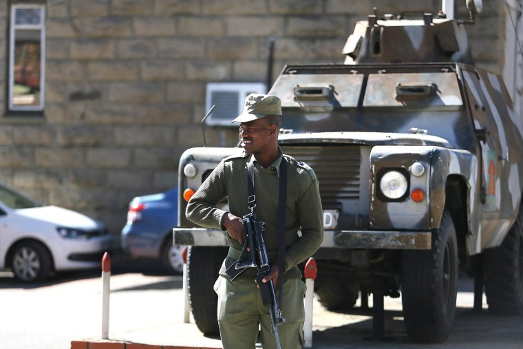 Image: A member of the Lesotho military stands guard alongside an military vehicle in Maseru, Lesotho