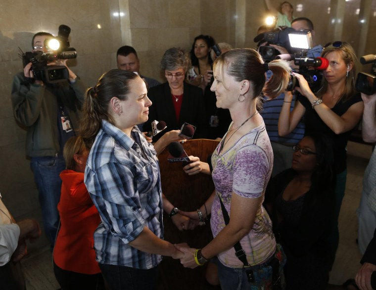 Image: Jill Winkler, left, and Pamela Dietzler hold hands as they are married at the Milwaukee County Courthouse