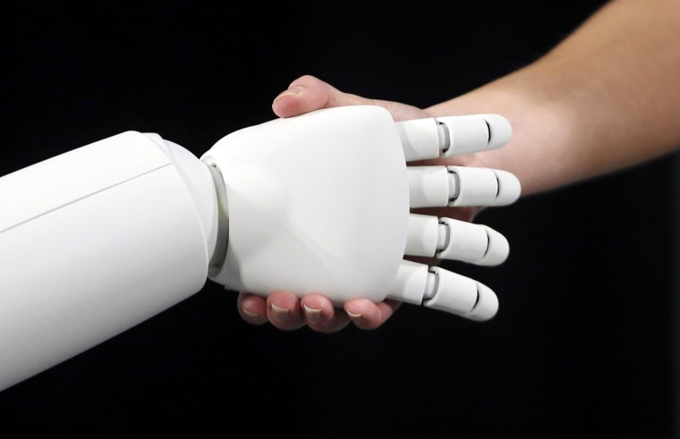 Image: Honda's latest version of the Asimo humanoid robot shakes hands during a presentation in Zaventem near Brussels