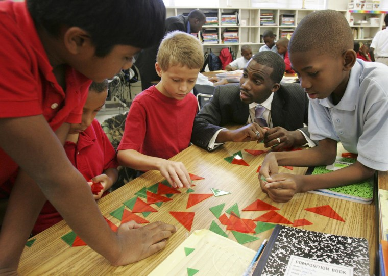 Image: Hayward Jean, 27, center, works with his fourth grade single gender students during a math lesson