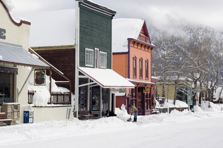 Image: A man shovels the walkway in front of his fly fishing shop in Crested Butte, Colo.