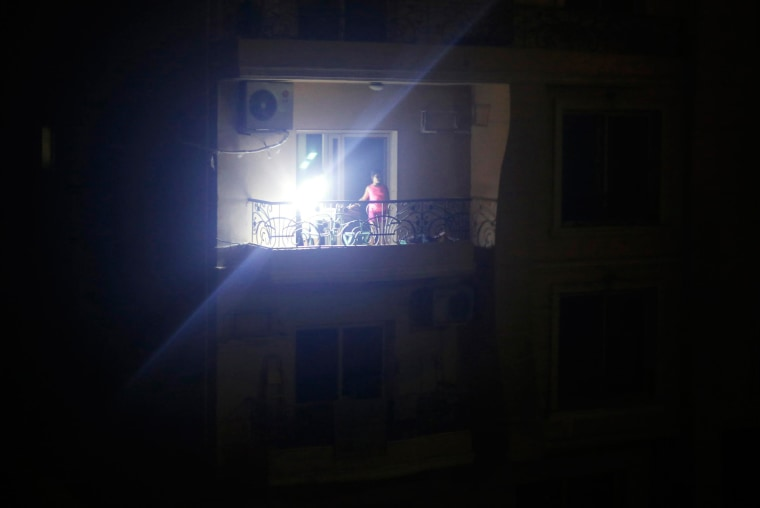 Image: A family uses an emergency light at the balcony of their house during a power cut conducted in Elmarag City in Maadi, Cairo