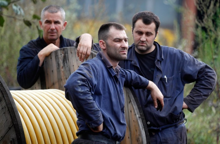Image: Miners stand in front of the Raspotocje coal mine in Zenica
