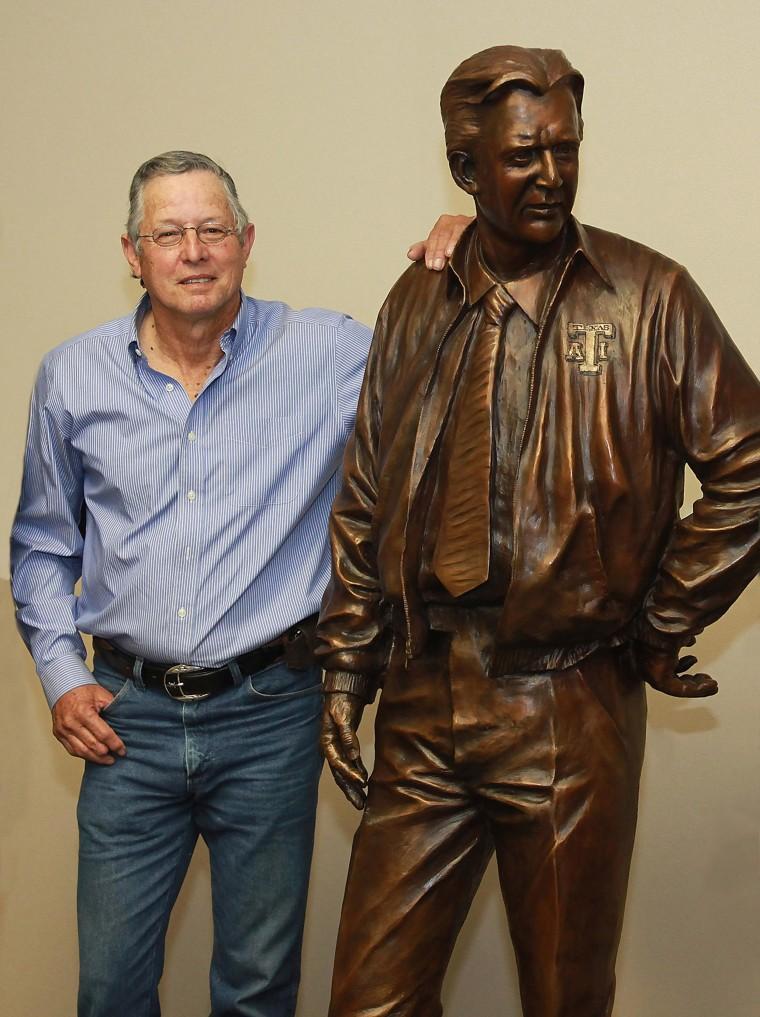 Sculptor Armando Hinojosa poses next to his life-size sculptor of legendary Texas college football coach Gil Steinke.