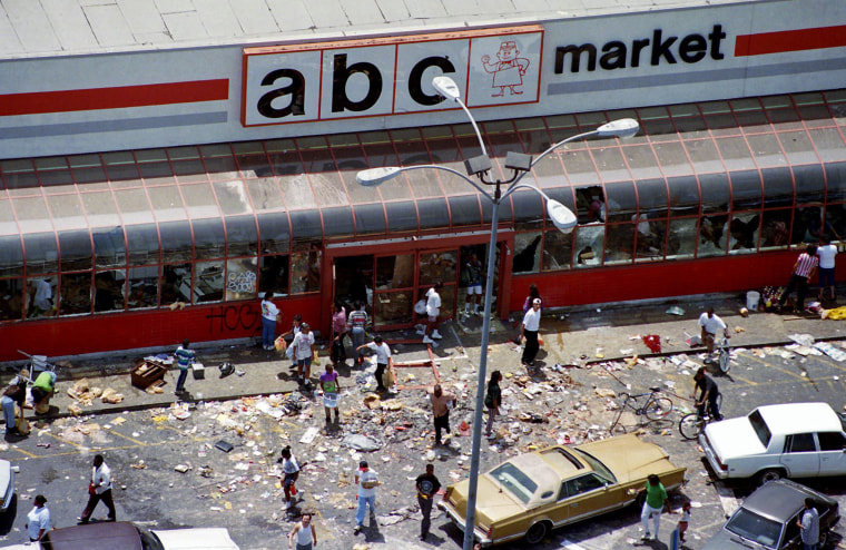 Looters mill in the parking lot of the ABC Market in South-Central Los Angeles as violence and looting ensued on the first day of riots following the verdicts in the Rodney King assault case, on April 30, 1992.