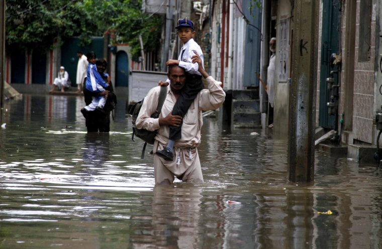 Pakistanis wade down a flooded road following heavy downpours in Rawalpindi, Pakistan.
