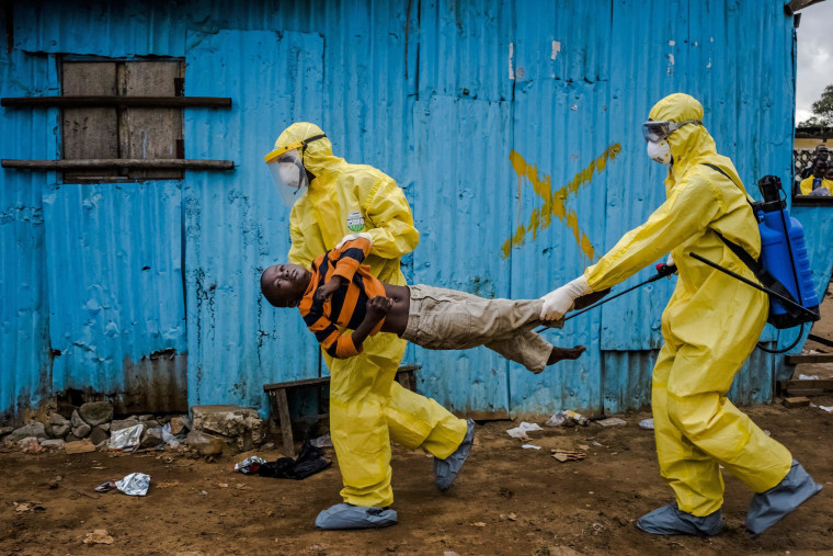Medical staff carry James Dorbor, 8, suspected of having Ebola, into a treatment facility in Monrovia, Liberia, on Friday. The fear sparked by the Ebola outbreak is having a serious economic impact on Guinea, Liberia and Sierra Leone, three nations already at the bottom of global economic and social indicators.