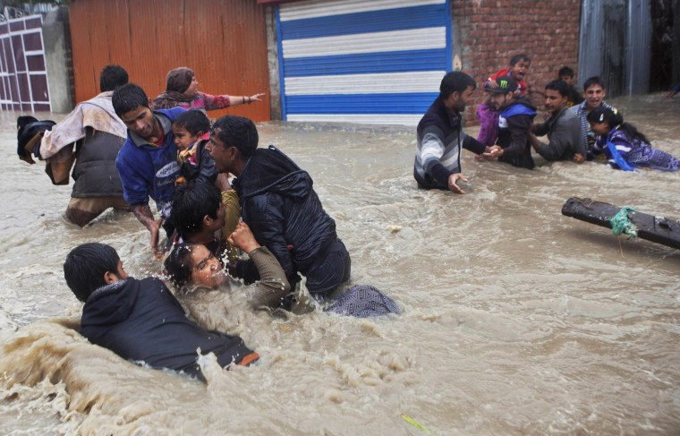 Image: Kashmiri residents wade through floodwaters in Srinagar, India