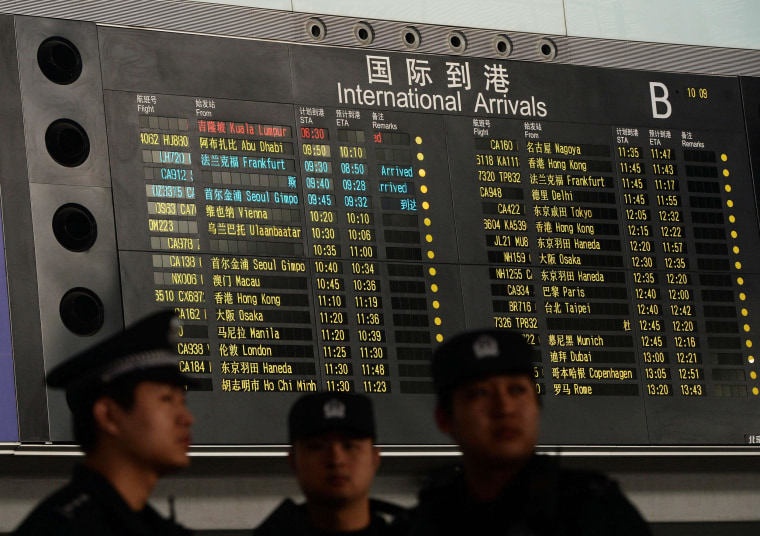 Chinese police stand beside the arrival board showing the flight MH370 (top) at the Beijing Airport after news of the Malaysia Airlines Boeing 777-200 plane disappeared on March 8, 2014. Malaysia Airlines said a flight carrying 239 people from Kuala Lumpur to Beijing went missing early on March 8, and the airline was notifying next of kin in a sign it expected the worst.