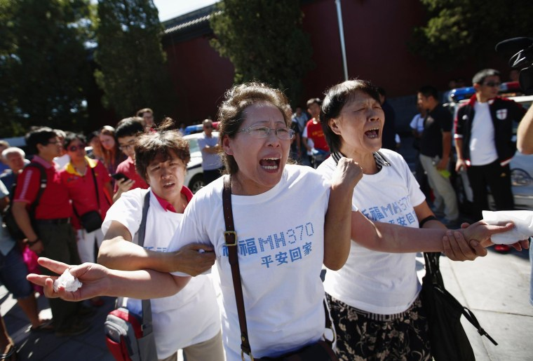 Family members of passengers on Malaysia Airlines Flight MH370 cry as they gather to pray at Yonghegong Lama Temple in Beijing September 8, 2014, on the six-month anniversary of the disappearance of the plane.