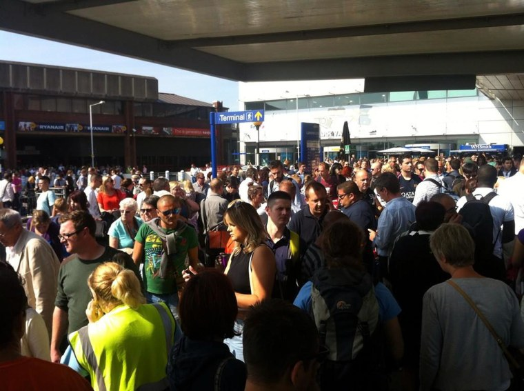 Passengers crowd outside Luton airport after a security alert.