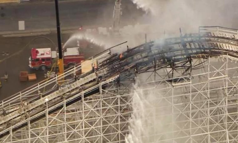 Image: Firefighters work to extinguish a fire on roller coaster tracks.