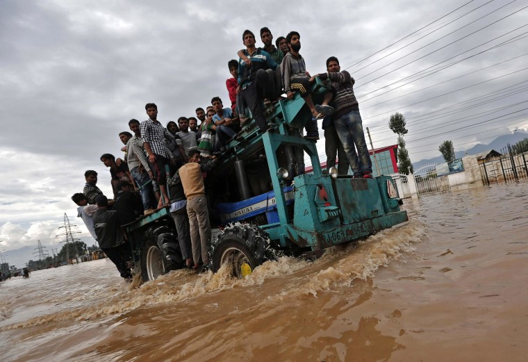 Image: A tractor evacuating Kashmiri flood victims to higher grounds travels through a flooded street in Srinagar