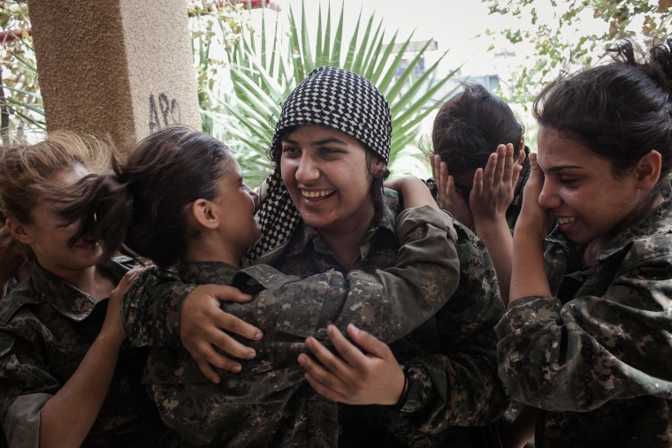 Image: Young YPJ recruits cry and embrace a fellow soldier who they thought had been sent to the front line