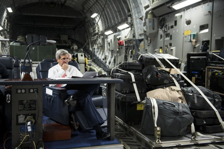 Image: U.S. Secretary of State John Kerry looks over papers while flying from Jordan to Iraq