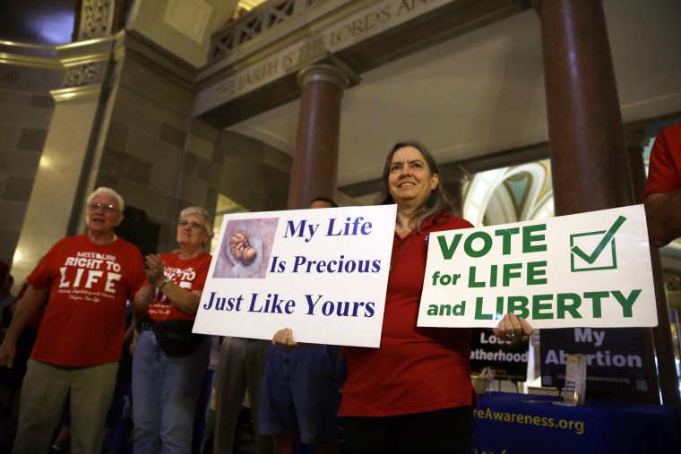 Image: Joanne Schrader holds signs as she gathers with other abortion opponents in the rotunda of the Missouri Capitol