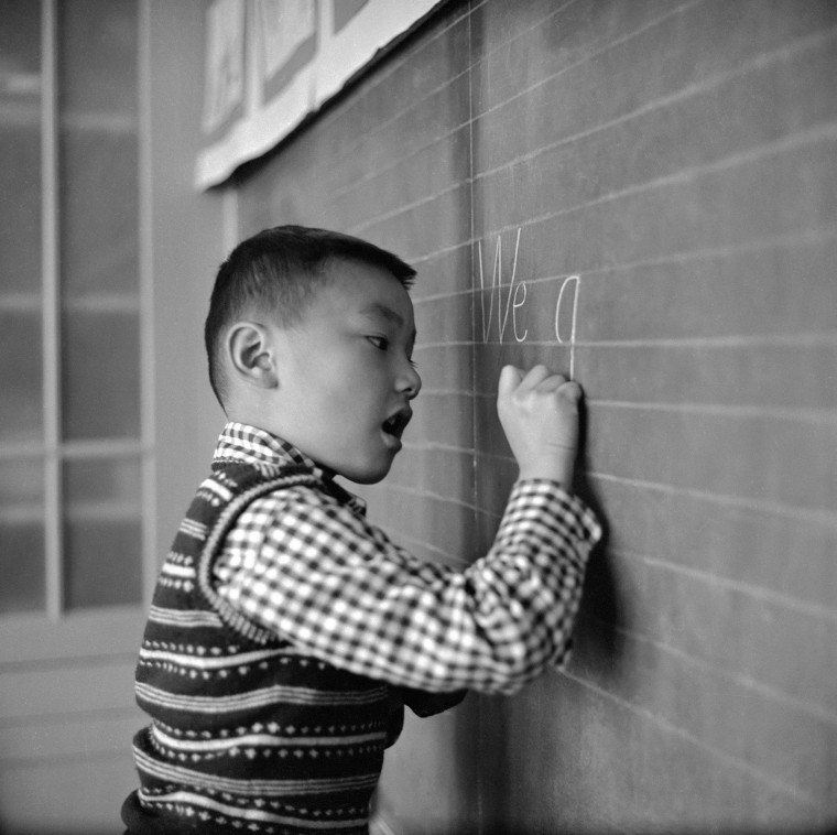 A Chinese boy writes carefully on the blackboard during an English lesson at the Commodore Stockton School in San Francisco's Chinatown in 1955.