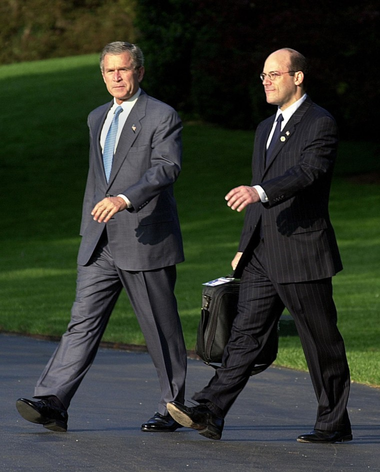 Then-President George W. Bush, with Press Secretary Ari Fleischer, walks accross the South Lawn 08 May 2002 to board Marine One at the White House in Washington, DC. Bush is scheduled to speak about education during his two stops in Wisconsin.