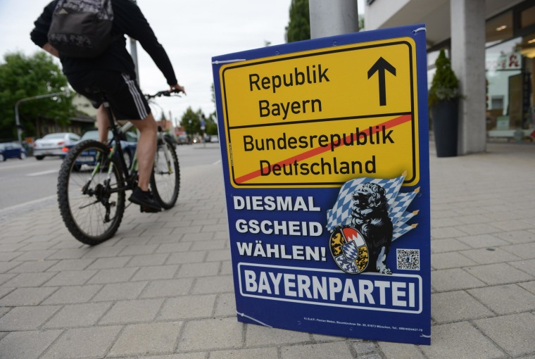 A cyclist passes a campaign poster of the Bavaria party in Dachau on Sept. 2, 2013. The poster shows a montage of typical German town signs with 'Federal Republic of Germany' crossed out and an arrow pointing towards 'Republic Bavaria'. A slogan in local