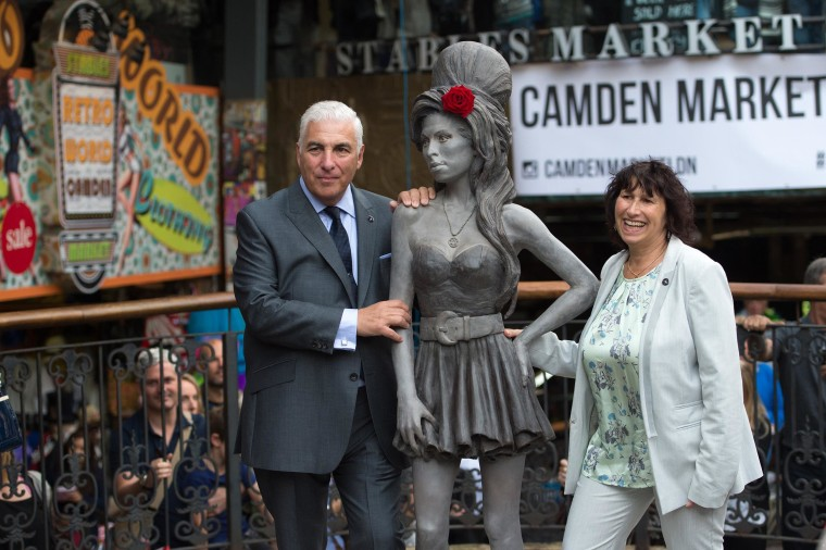 Image: Mitch Winehouse and Janis Winehouse pose for a picture with a statue of their late daughter, Amy Winehouse