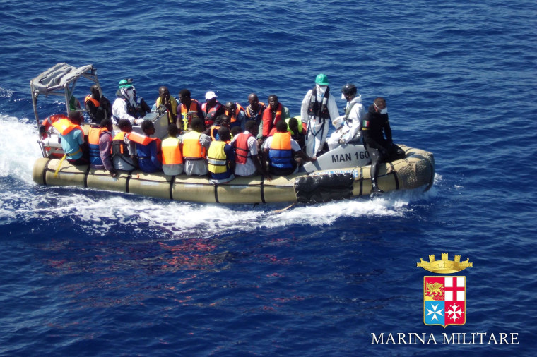 Migrants sit in a boat during a rescue operation off the coast of Sicily on Sunday.