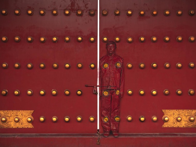 "Liu Bolin ""disappears"" into a red door in this photograph, part of his ""Hiding in the City"" series."