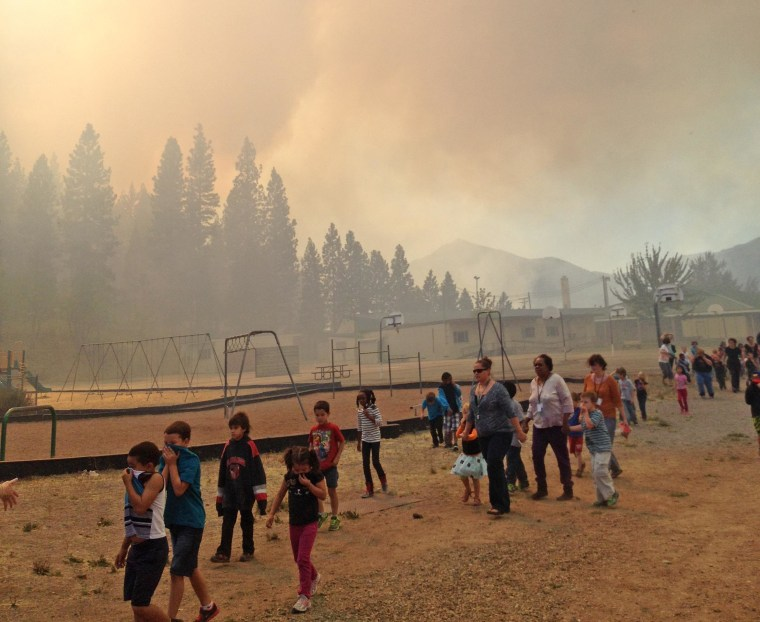 Children are evacuated from the Weed Elementary School in Weed, Calif., as a wildfire burns nearby on Sept. 15, 2014.