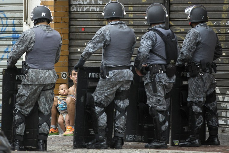 Image: A man and a baby, who voluntarily left an occupied building, are framed by the shields of police standing guard during an eviction operation