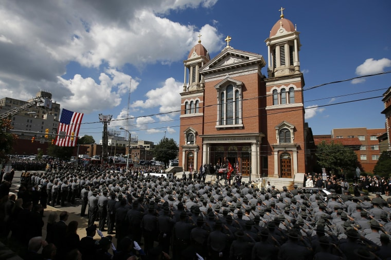 An honor guard carries the casket of Pennsylvania State Trooper Cpl. Bryon Dickson after his funeral service, on Sept. 18, in Scranton, Pa.