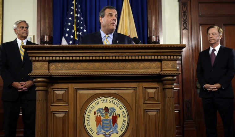 Richard Mroz, left, and Jamie Fox, right, listens as New Jersey Gov. Chris Christie announces that he has chosen Fox, the former top aide to Democratic Gov. Jim McGreevey to be New Jersey's new transportation commissioner and Mroz to be president of the Board of Public Utilities, Thursday, Sept. 18, 2014, in Trenton, N.J. (AP Photo/Mel Evans)