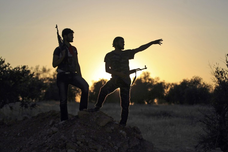 Image: Free Syrian Army fighters are silhouetted as they stand on one of the front lines of Wadi Al-Daif camp in the southern Idlib countryside