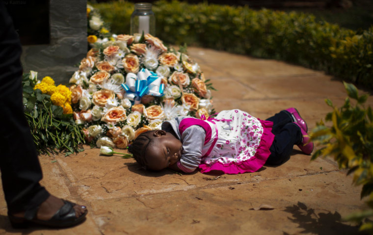 Image: Nicole Tashly, 2, lies quietly on the ground holding a white rose