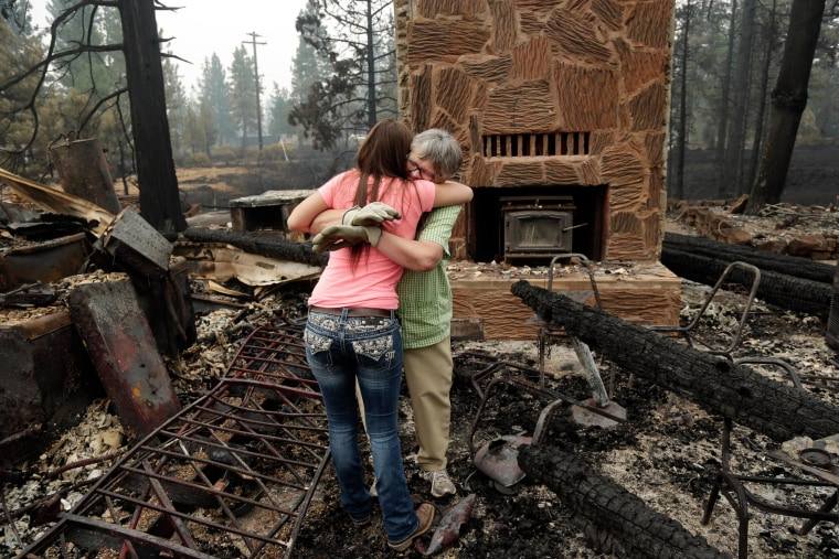 Donna Garner, right, embraces former employee Napua Gonsales-Merck while they shift through the remains of the Fireside Village restaurant and shop in the aftermath of the Eiler Fire in Hat Creek, Calif., on Aug. 5, 2014.