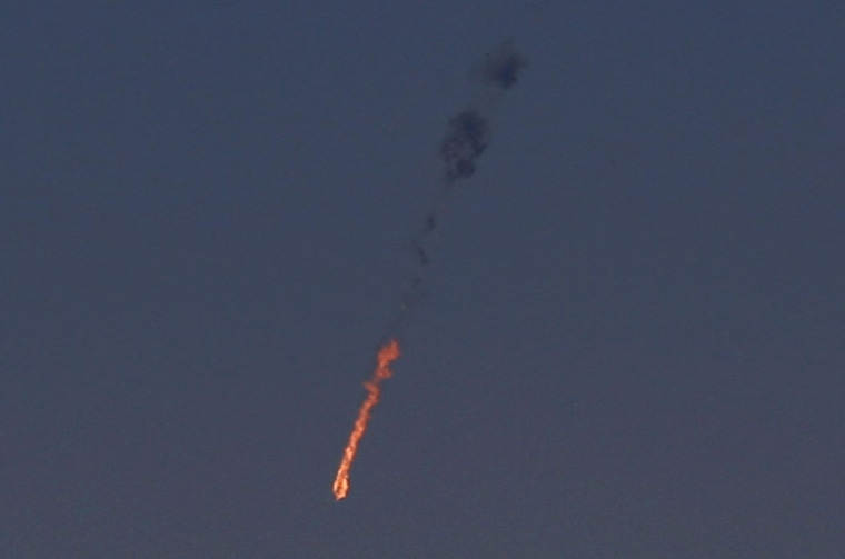 Image: A Syrian fighter jet is seen in flames after it was hit by the Israeli military over the Golan Heights